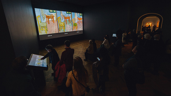 "Viewers watch motion graphics comparing Van Gogh's ""Bedroom"" paintings in the conservation documentary ""Inside the Bedroom"" at the Art Institute of Chicago."