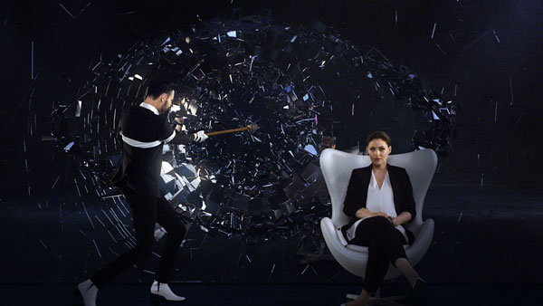 Rylan Clark-Neal smashes a sledgehammer against an enormous mirror, shattering it into the form of the new Big Brother logo. The shards of glass then fly out past the Clark-Neal and fellow presenter Emma Willis towards the screen.